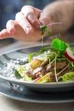 Шеф-повар в кухне гостиницы или ресторана варя, только руки Он работает на микро- украшении травы подготовлять овощ салата стоковое изображение rf
