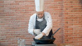 Шеф-повар в ресторане варя зажаренный вареник с морепродуктами в лотке, сжимая лимонный сок Стоковое фото RF