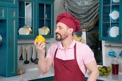 Шеф-повар в рисберме и крышка обнюхивая желтую паприку и улыбку лучей стоковые фотографии rf