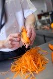 Шеф-повар в форме подготавливая свежие жезлы моркови Стоковые Изображения