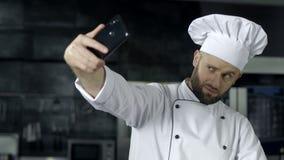 Шеф-повар делая фото на кухне Портрет шеф-повара принимая selfie на мобильный телефон акции видеоматериалы