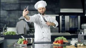 Шеф-повар делая фото на кухне Шеф-повар с ножом принимая selfie на мобильный телефон акции видеоматериалы
