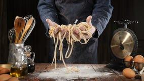 Среднеземноморская концепция кухни Шеф-повар держа свежие макаронные изделия на деревянной доске, утвари кухни вокруг, совсем сде акции видеоматериалы
