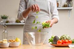 Шеф-повар добавляет зеленые листья салата, шевелит, в процессе вегетарианского салата в домашней кухне : o стоковые изображения