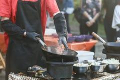 Шеф-повар добавляя ингридиенты в вке литого железа Стоковое Фото