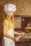 Шеф-повар девушки положил пиццу в горячую печь на ресторане Стоковые Изображения RF
