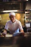 Шеф-повар держа цифровую таблетку и заказ перечисляют в коммерчески кухне Стоковые Изображения