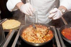 шеф-повар жаря мидий стоковые фото