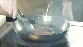 Шеф-повар жаря поднимающее вверх мяса близкое видеоматериал
