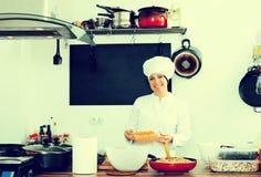 Шеф-повар женщины варя еду на кухне кафа Стоковое Фото