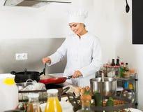 Шеф-повар женщины варя еду на кухне Стоковое Изображение RF