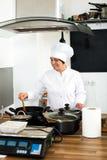 Шеф-повар женщины варя еду на кухне ` s кафа Стоковое фото RF