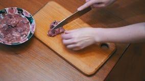 Шеф-повар женщины отрезает мясо куриной печени на деревянной доске кухни в домашней кухне видеоматериал