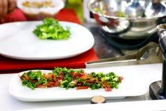 Шеф-повар заканчивая ее плиту и почти подготавливает для служения на таблице Только руки В конце концов шлихта блюда: мясо стейка стоковые фото