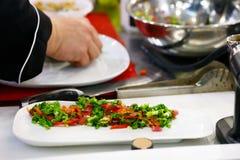 Шеф-повар заканчивая ее плиту и почти подготавливает для служения на таблице Только руки В конце концов шлихта блюда: мясо стейка стоковая фотография rf
