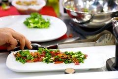 Шеф-повар заканчивая ее плиту и почти подготавливает для служения на таблице Только руки В конце концов шлихта блюда: мясо стейка стоковая фотография