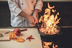 Шеф-повар зрелого человека профессиональный варя еду внутри помещения Стоковое фото RF