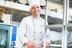Шеф-повар или кашевар в кухне гостиницы варя блюда стоковые фотографии rf