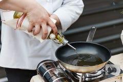 Шеф-повар лить масло Розмари в лотке, подготавливает для того чтобы сварить стоковое изображение rf