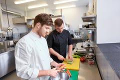 Шеф-повар и кашевар варя еду на кухне ресторана Стоковая Фотография