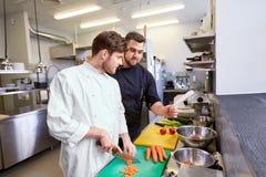 Шеф-повар и кашевар варя еду на кухне ресторана Стоковые Изображения RF