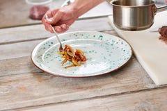 Шеф-повар кладя овощи от кастрюльки на плиту Стоковое фото RF