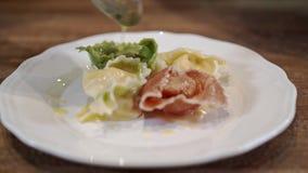 Шеф-повар кладя tortellini других цветов на плиту и украшая его акции видеоматериалы