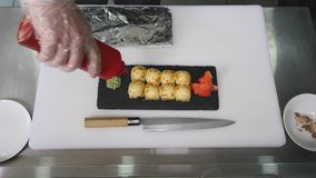 Шеф-повар кладет имбирь на плиту суш, конец-вверх белизна суш половика предпосылки bamboo варя сток-видео