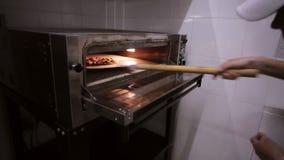 Шеф-повар кладет сырцовую пиццу в печь в коммерчески кухне видеоматериал