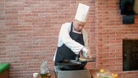 Шеф-повар кладя зажаренные вареники с морепродуктами на плиту сток-видео