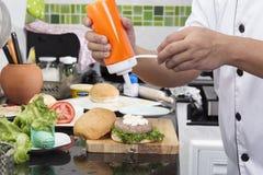 Шеф-повар кладя майонез на плюшку гамбургера Стоковое фото RF