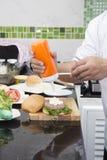 Шеф-повар кладя майонез на плюшку гамбургера Стоковая Фотография RF