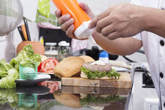 Шеф-повар кладя майонез на плюшку гамбургера Стоковые Фотографии RF