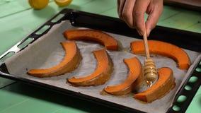 Шеф-повар льет мед на испеченных кусках тыквы видеоматериал