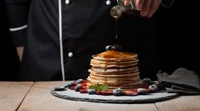 Шеф-повар льет сироп клена на стоге блинчика с голубиками и клубниками на черной предпосылке стоковые фотографии rf