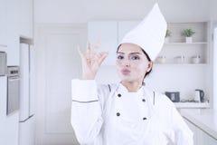 Шеф-повар молодой женщины показывая ОДОБРЕННЫЙ знак Стоковые Изображения RF