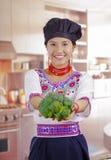 Шеф-повар молодой женщины нося традиционную андийскую блузку, шляпу черной варки, держа брокколи вверх показывая к камере и усмех Стоковые Фото