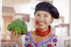 Шеф-повар молодой женщины нося традиционную андийскую блузку, шляпу черной варки, держа брокколи вверх показывая к камере и усмех Стоковые Фотографии RF
