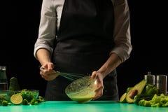 Шеф-повар на черной предпосылке взбивает сок от овощей для варить зеленые smoothies detoxification Здоровая, чистая еда, потеря в стоковое изображение rf