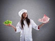Шеф-повар нерешительный между свежими салатом или стейком мяса концепция вегетарианца стоковые фотографии rf