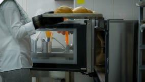 Шеф-повар нося белую форму раскрывает дверь печи вытягивает вне поднос свеже испеченных кренов Подготовка очень вкусного сток-видео