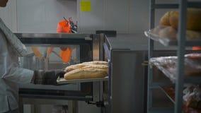 Шеф-повар нося белую форму раскрывает дверь печи вытягивает вне поднос свеже испеченных кренов Подготовка очень вкусного видеоматериал