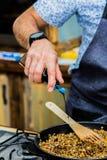 Шеф-повар добавляет ингридиенты к едам Стоковые Фотографии RF