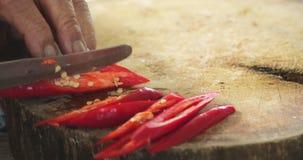 Шеф-повар отрезает перец красных чилей Резать перца красных чилей видеоматериал