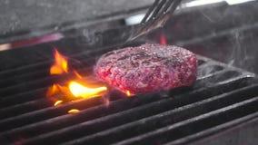 Шеф-повар поворачивает сырое мясо для бургера на горячем гриле Серии огня и дыма Конец-вверх, замедленное движение акции видеоматериалы