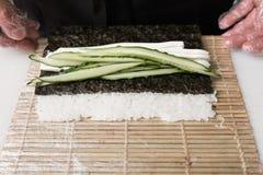 Шеф-повар подготавливает ингридиенты огурца крена суш свежие Стоковые Фотографии RF