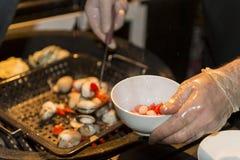 Шеф-повар подготавливает морепродукты, мидий, кладет еду в блюдо Стоковое Фото