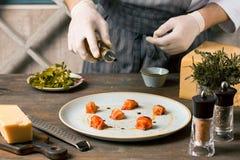 Шеф-повар подготавливая еду в кухне ресторана босс мочит salmon carpaccio с оливковым маслом стоковое изображение