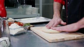 Шеф-повар подготавливая тесто для пиццы с завальцовкой оно в муке сток-видео