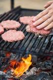 Шеф-повар подготавливая бургеры на барбекю outdoors Стоковая Фотография